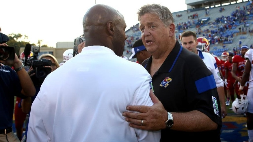 Texas head coach Charlie Strong, front, and Kansas head coach Charlie Weis meet on the field after an NCAA football game Saturday, Sept. 27, 2014, in Lawrence, Kan. Texas won 23-0. (AP Photo/Ed Zurga)