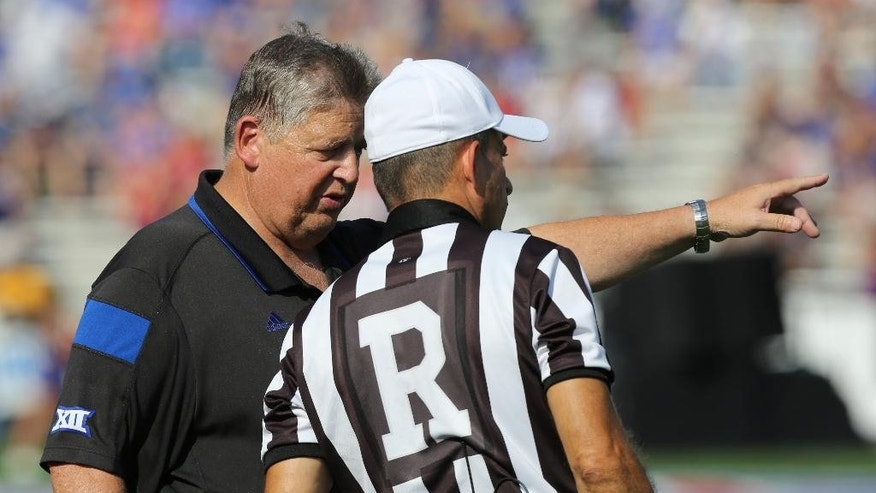 Kansas head coach Charlie Weis talks with referee Rick Loumiet after a penalty call in the first quarter during an NCAA football game against the Texas Saturday, Sept. 27, 2014, in Lawrence, Kan. (AP Photo/Ed Zurga)
