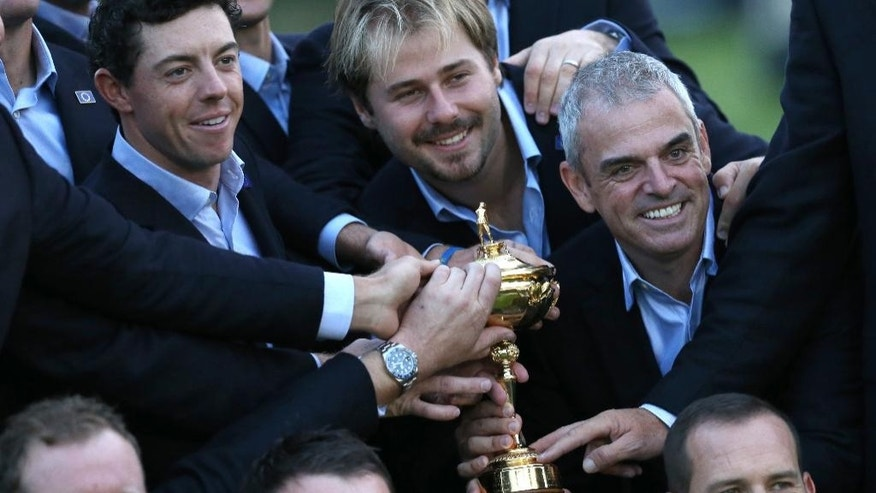 Europe team captain Paul McGinley, right, and his team, including Sergio Garcia, bottom right, Graeme McDowell, center front, Jamie Donaldson, left, Rory McIlroy, top left, and Victor Dubuisson, top center, hold the trophy after winning the 2014 Ryder Cup golf tournament at Gleneagles, Scotland, Sunday, Sept. 28, 2014. (AP Photo/Peter Morrison)