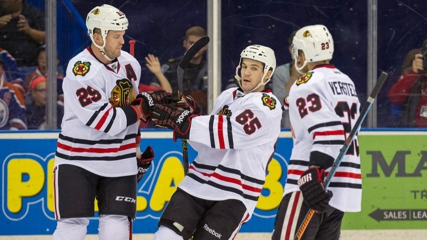 Chicago Blackhawks Bryan Bickell, left, is congratulated on his goal by teammates Andrew Shaw, center, and Kris Versteeg during first period NHL pre-season action against the Edmonton Oilers in Saskatoon, Saskatchewan, Canada, Sunday, Sept 28, 2014. (AP Photo/The Canadian Press, Liam Richards)