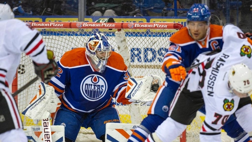 Edmonton Oilers goalie Richard Bachman makes a glove save as Andrew Ference battles for positions with Chicago Blackhawks, center, Dennis Rasmussen during first period NHL pre-season action in Saskatoon, Saskatchewan, Canada, Sunday, Sept 28, 2014. (AP Photo/The Canadian Press, Liam Richards)