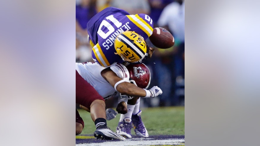LSU quarterback Anthony Jennings (10) fumbles as he is hit by New Mexico State defensive back Kawe Johnson on a carry in the first half of an NCAA college football game in Baton Rouge, La., Saturday, Sept. 27, 2014. (AP Photo/Gerald Herbert)
