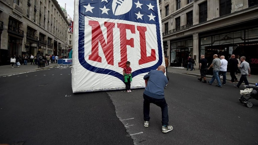 A boy poses for a picture during NFL on Regent Street, a fan rally event on Regent Street, London, England, Saturday, Sept. 27, 2014.  The Oakland Raiders will play the Miami Dolphins in an NFL football game at London's Wembley Stadium on Sunday Sept. 28. (AP Photo/Tim Ireland)