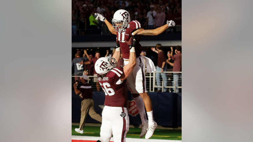 Texas A&M offensive linesman Mike Matthews (56) lifts wide receiver Josh Reynolds (11) as the two celebrate a 59-yard-touchdown scored by Reynolds to tie Arkansas late in the second half of an NCAA college football game, Saturday, Sept. 27, 2014, in Arlington, Texas. Texas A&M won in overtime 35-28. (AP Photo/Tony Gutierrez)