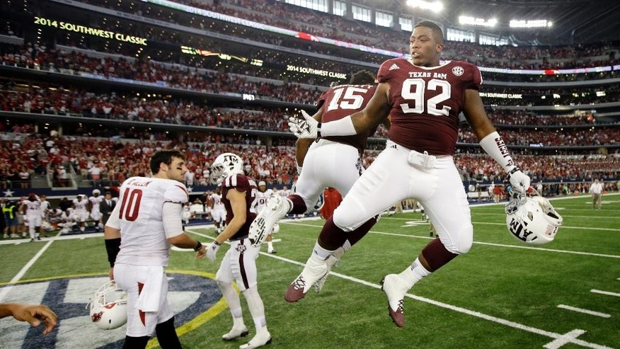 Arkansas quarterback Brandon Allen (10) watches as Texas A&M's Zaycoven Henderson (92) and defensive lineman Myles Garrett (15) celebrate their 35-28 overtime win in an NCAA college football game, Saturday, Sept. 27, 2014, in Arlington, Texas. (AP Photo/Tony Gutierrez)