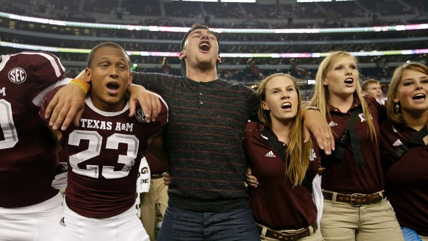 Cleveland Browns quarterback and former Texas A&M quarterback Johnny Manziel, center, joins the Armani Watts (23), and the rest of the team and staff as they sing the Aggie War Hymn after the Aggies 35-28 overtime win against Arkansas in an NCAA college football game, Saturday, Sept. 27, 2014, in Arlington, Texas. (AP Photo/Tony Gutierrez)