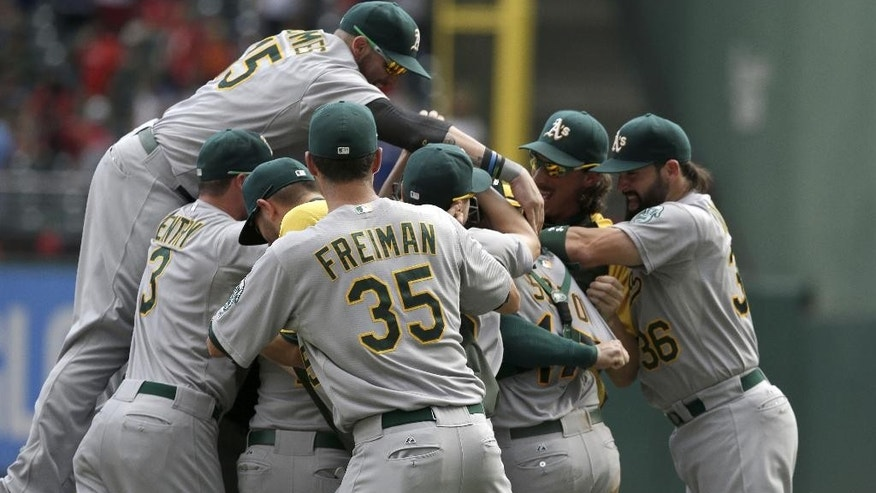 Oakland Athletics starting pitcher Sonny Gray is mobbed by his teammates after the final out of  the baseball game against the Texas Rangers clinching a playoff spot Sunday, Sept. 28, 2014,  in Arlington, Texas.  The Athletics won 4-0.  (AP Photo/LM Otero)