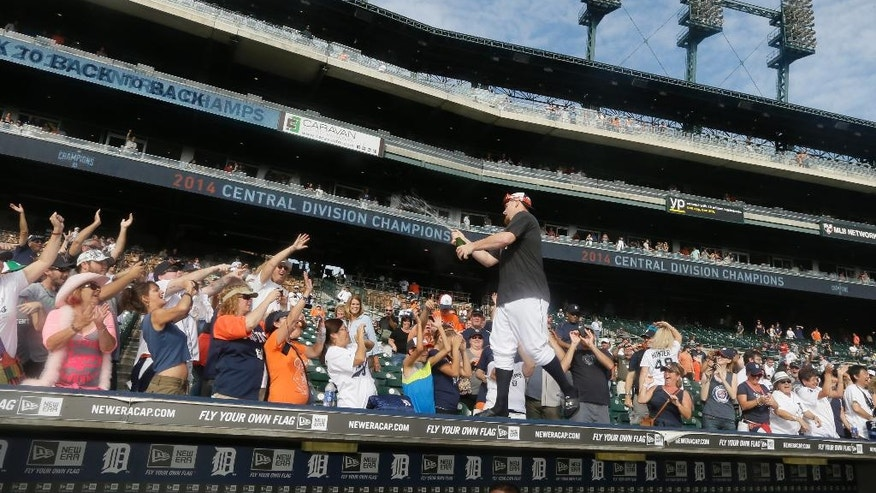 Detroit Tigers relief pitcher Phil Coke stands on top of the dugout and celebrates with fans after the Tigers clinched the AL Central with a 3-0 win over the Minnesota Twins in a baseball game in Detroit, Sunday, Sept. 28, 2014. (AP Photo/Carlos Osorio)