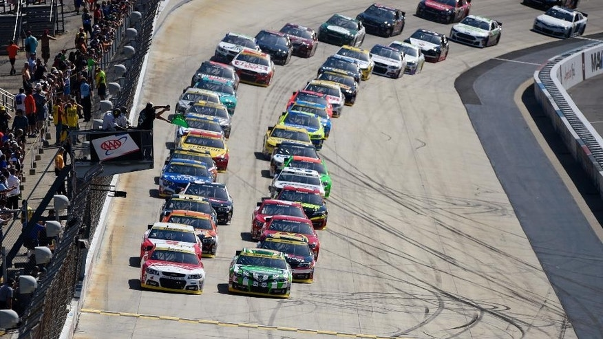The field led by Kevin Harvick, left front, and Kyle Busch, right front, takes the green flag for the start of the NASCAR Sprint Cup series auto race, Sunday, Sept. 28, 2014, at Dover International Speedway in Dover, Del. (AP Photo/Nick Wass)