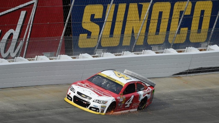 Sparks fly from the car of Kevin Harvick as a tire starts to go down during the NASCAR Sprint Cup series auto race, Sunday, Sept. 28, 2014, at Dover International Speedway in Dover, Del. (AP Photo/Nick Wass)
