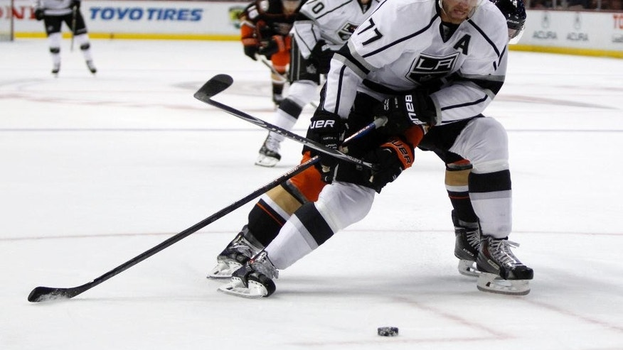 Los Angeles Kings center Jeff Carter (77) controls the puck to take a shot with Anaheim Ducks defenseman Cam Fowler (4) defending during the first period of a preseason NHL hockey game, Sunday, Sept. 28, 2014, in Anaheim, Calif. (AP Photo/Alex Gallardo)