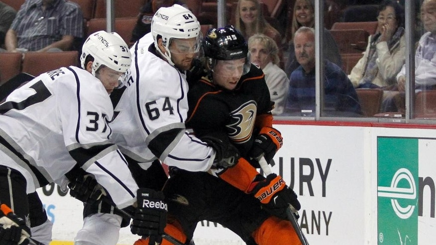 Los Angeles Kings center Nick Shore (37) and left wing Andy Andreoff (64) scrap for the puck with Anaheim Ducks defenseman Sami Vatanen (45), of Finland, during the first period of a preseason NHL hockey game, Sunday, Sept. 28, 2014, in Anaheim, Calif. (AP Photo/Alex Gallardo)