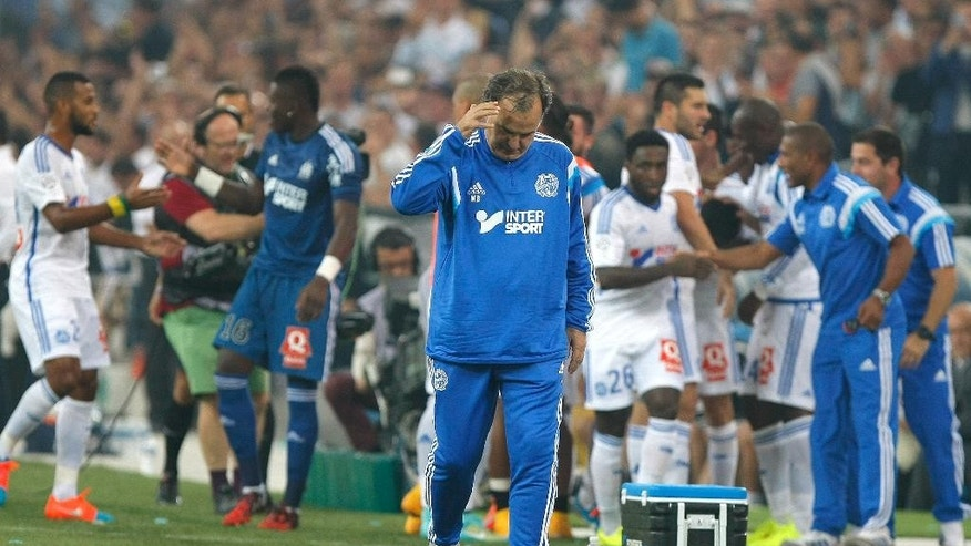 Marseille's Argentinian coach Marcelo Bielsa reacts as Marseille's players celebrate after Marseille's French midfielder Giannelli Imbula scored against Saint-Etienne during their League One soccer match, at the Velodrome Stadium, in Marseille, southern France, Sunday, Sept. 28, 2014. (AP Photo/Claude Paris)