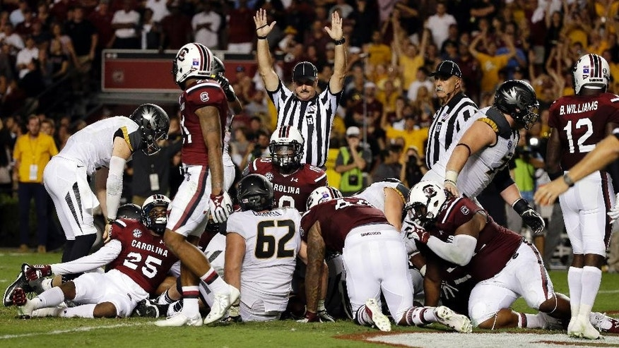 An official signals a touchdown after Missouri running back Russell Hansbrough drives the pile into the end zone during the second half of an NCAA college football game against South Carolina on Saturday, Sept. 27, 2014, in Columbia, S.C. Missouri won 21-20.  (AP Photo/Stephen B. Morton)
