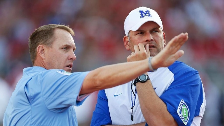 Mississippi coach Hugh Freeze, left, talks with Memphis coach Justin Fuentes before an NCAA college football game against Memphis in Oxford, Miss., Saturday, Sept. 27, 2014.  (AP Photo/Rogelio V. Solis)