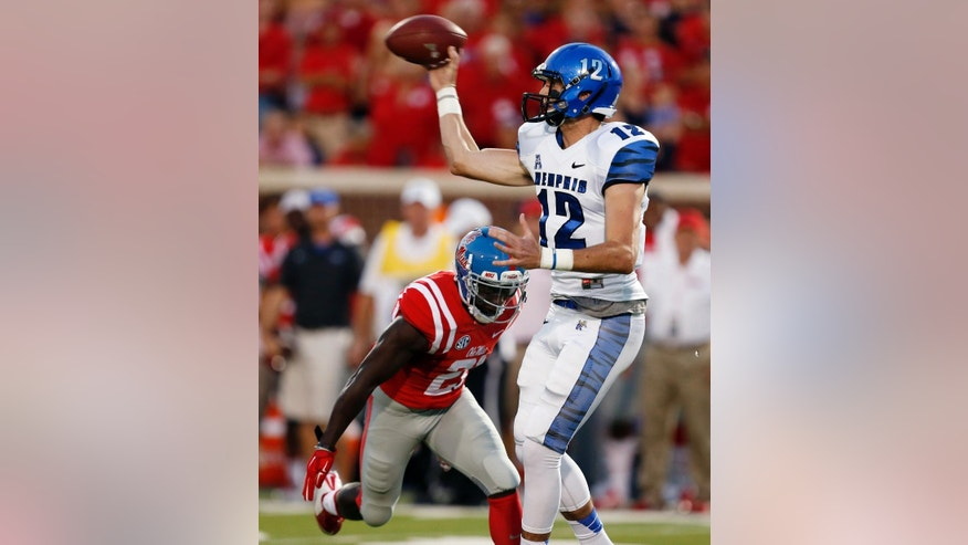 Memphis quarterback Paxton Lynch (12) passes as Memphis defensive back Bobby McCain (21) closes in during the first half of an NCAA college football game in Oxford, Miss., Saturday, Sept. 27, 2014. (AP Photo/Rogelio V. Solis)