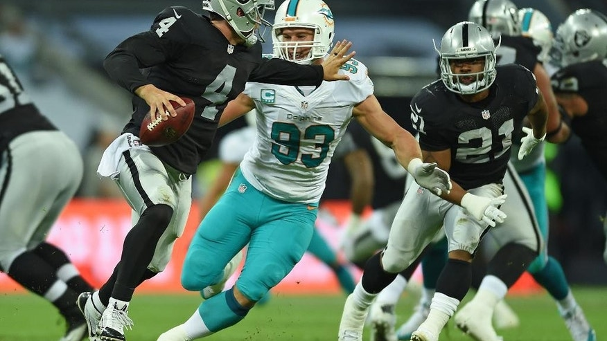 Oakland Raiders' Derek Carr, left, tries to fend off Miami Dolphins' Jason Trusnik during the NFL football game at Wembley Stadium in London, Sunday, Sept. 28, 2014. (AP Photo/Tim Ireland)