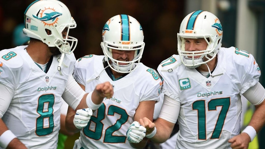 Miami Dolphins' Ryan Tannehill, right, Matt Moore, left, and Brian Hartline run onto the field to warm up before the NFL football game against Oakland Raiders at Wembley Stadium in London, Sunday, Sept. 28, 2014. (AP Photo/Tim Ireland)