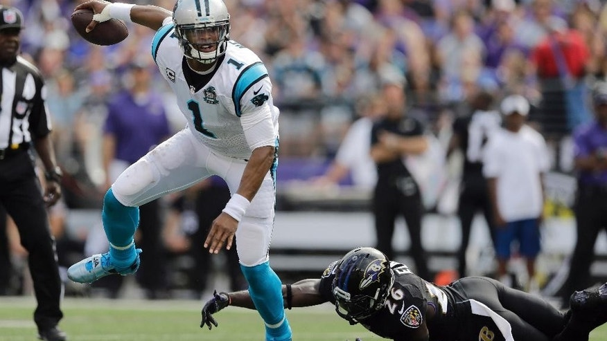 Carolina Panthers quarterback Cam Newton (1) breaks free from Baltimore Ravens strong safety Matt Elam (26) during the first half of an NFL football game in Baltimore, Sunday, Sept. 28, 2014. (AP Photo/Patrick Semansky)