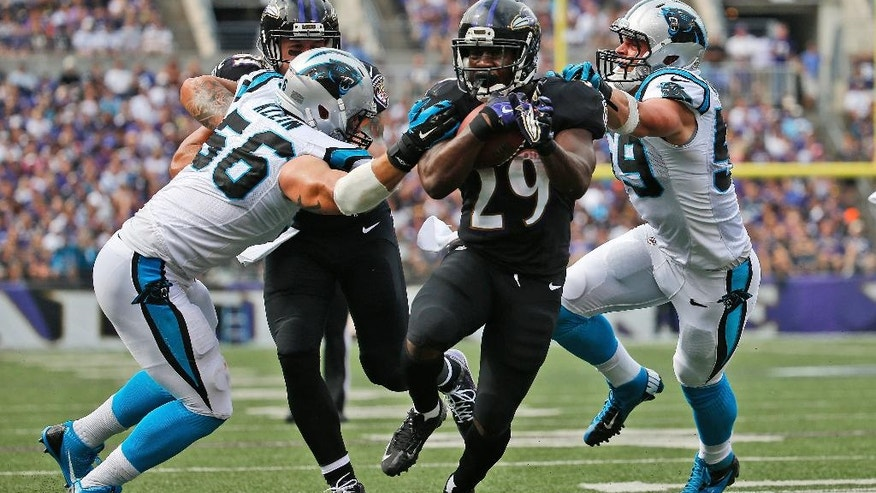 Baltimore Ravens running back Justin Forsett (29) breaks a tackle by Carolina Panthers outside linebacker A.J. Klein (56) and middle linebacker Luke Kuechly (59) and runs for a touchdown during the first half of an NFL football game in Baltimore, Sunday, Sept. 28, 2014. (AP Photo/Evan Vucci)