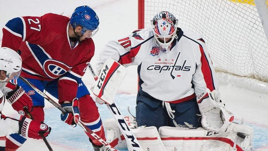 Washington Capitals goaltender Braden Holtby makes a save against Montreal Canadiens Alex Galchenyuk (27) during the second period of an NHL hockey preseason game Sunday, Sept. 28, 2014, in Montreal. (AP Photo/Graham Hughes)