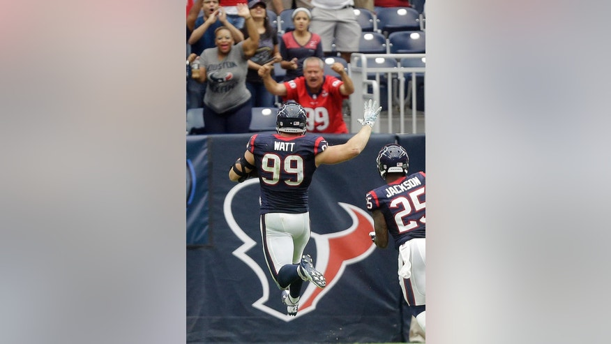 Houston Texans' J.J. Watt (99) celebrates as he returns an interception for a touchdown against the Buffalo Bills during the third quarter of an NFL football game, Sunday, Sept. 28, 2014, in Houston. (AP Photo/Patric Schneider)