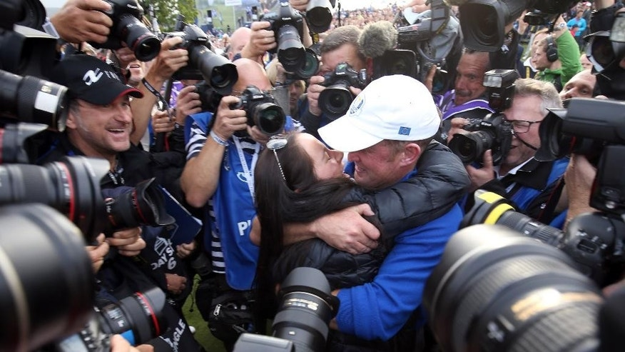 Europe's Jamie Donaldson and his fiancee Kathryn Tagg, surrounded by the media, celebrate winning the 2014 Ryder Cup golf tournament at Gleneagles, Scotland, Sunday, Sept. 28, 2014. (AP Photo/Peter Morrison)