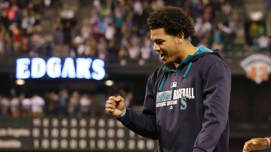 Seattle Mariners pitcher Felix Hernandez pumps his fist as he walks off the field after the Mariners defeated the Los Angeles Angels 2-1 in 11 innings in a baseball game, Saturday, Sept. 27, 2014, in Seattle. (AP Photo/Ted S. Warren)