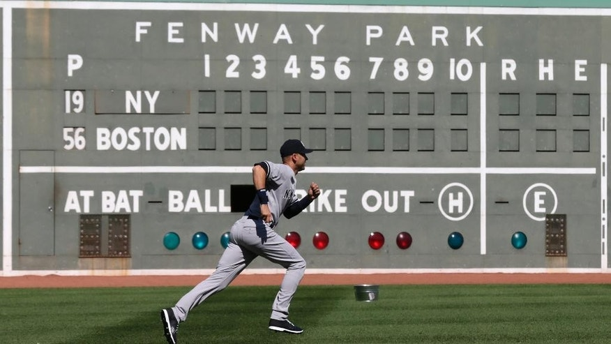 New York Yankees designated hitter Derek Jeter runs in left field as he prepares to face the Boston Red Sox in a baseball game at Fenway Park in Boston, Saturday, Sept. 27, 2014. (AP Photo/Charles Krupa)