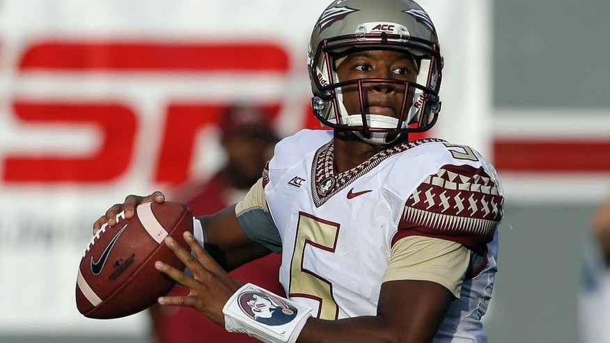 Florida State quarterback Jameis Winston (5) looks to pass against North Carolina State during the second half of an NCAA college football game in Raleigh, N.C., Saturday, Sept. 27, 2014. Florida State won 56-41.(AP Photo/Gerry Broome)