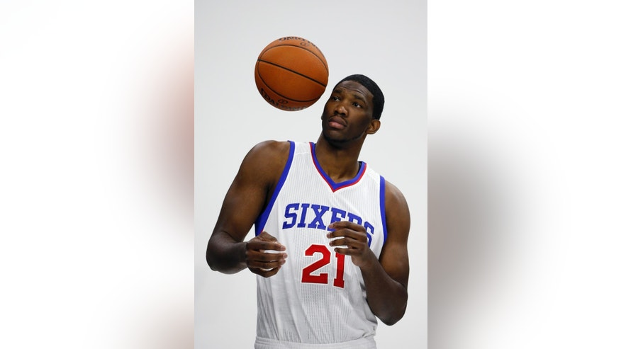 Philadelphia 76ers' Joel Embiid, of Cameroon, bounces a basketball off of his shoulder as he waits to pose for a photographer during the NBA basketball team's media day, Monday, Sept. 29, 2014, in Philadelphia. (AP Photo/Matt Slocum)