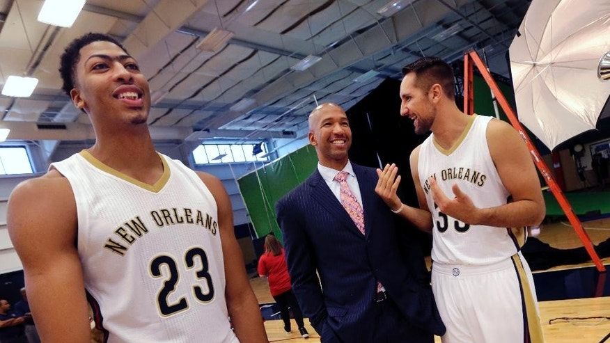 New Orleans Pelicans head coach Monty Williams, center, chats with Ryan Anderson (33) and Anthony Davis (23) as they wait for a group photo at the Pelicans NBA basketball media day in Metairie, La., Monday, Sept. 29, 2014. (AP Photo/Gerald Herbert)