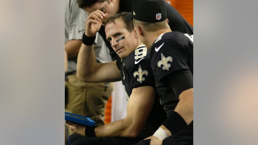 New Orleans Saints' Drew Brees (9) sits on the sideline during the first half of an NFL football game against the Dallas Cowboys, Sunday, Sept. 28, 2014, in Arlington, Texas. (AP Photo/Tim Sharp)