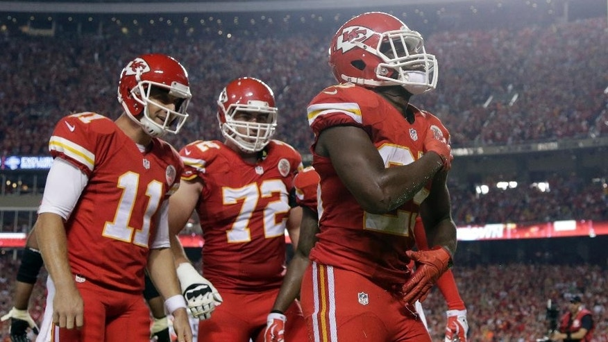 Kansas City Chiefs running back Jamaal Charles, right, brushes himself off as teammates Alex Smith, left, and Eric Fisher watch after scoring on an 8-yard touchdown pass during the third quarter of an NFL football game against the New England Patriots Monday, Sept. 29, 2014, in Kansas City, Mo. (AP Photo/Charlie Riedel)