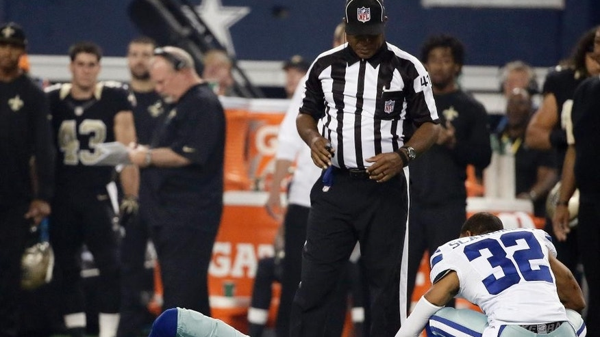 Field judge Boris Cheek (41) and Dallas Cowboys cornerback Orlando Scandrick (32) check on cornerback Morris Claiborne, who lies on the field during the first half of an NFL football game against the New Orleans Saints, Sunday, Sept. 28, 2014, in Arlington, Texas. (AP Photo/Brandon Wade)