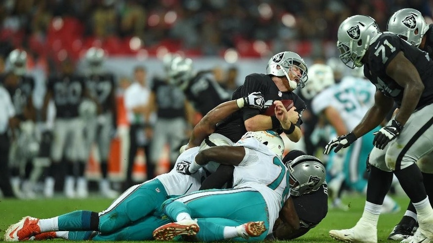 Oakland Raiders' Matt McGloin reacts as he is sacked during the NFL football game against Miami Dolphins at Wembley Stadium in London, Sunday, Sept. 28, 2014. (AP Photo/Tim Ireland)