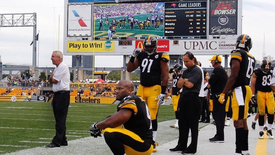 Pittsburgh Steelers' James Harrison (92) sits on his helmet on the sideline near the end of a 27-24 loss to the Tampa Bay Buccaneers in an NFL football game in Pittsburgh, Sunday, Sept. 28, 2014. (AP Photo/Gene J. Puskar)