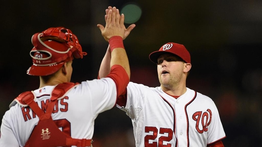 FILE - In this Sept. 23, 2014 file photo, Washington Nationals relief pitcher Drew Storen (22) gets a high-five from Washington Nationals catcher Wilson Ramos after the Nationals beat the New York Mets 4-2 in a baseball game, in Washington. The baseball playoffs are not only a second season but a second chance for the likes of Clayton Kershaw of the Dodgers, Adam Jones of the Orioles and Drew Storen of the Nationals to atone for past playoff flops.  (AP Photo/Nick Wass, File)