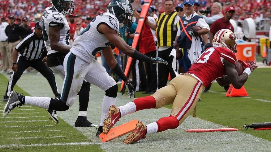 San Francisco 49ers wide receiver Steve Johnson, right, catches a 12-yard touchdown pass next to Philadelphia Eagles cornerback Cary Williams, center, and cornerback Nolan Carroll during the third quarter of an NFL football game in Santa Clara, Calif., Sunday, Sept. 28, 2014. (AP Photo/Marcio Jose Sanchez)