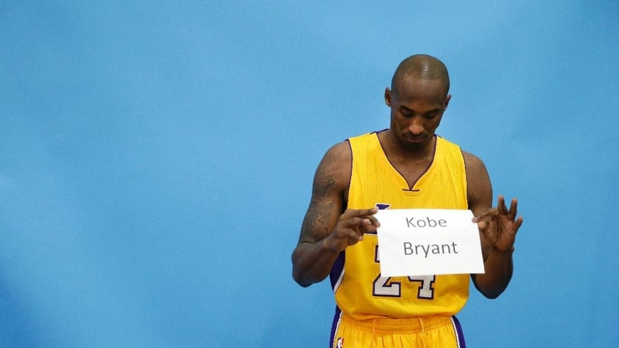 Los Angeles Lakers' Kobe Bryant holds his name card during a photo shoot on the team's NBA basketball media day Monday, Sept. 29, 2014, in El Segundo, Calif. (AP Photo/Jae C. Hong)