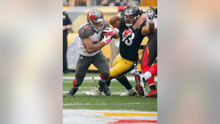 Tampa Bay Buccaneers running back Doug Martin (22) runs past Pittsburgh Steelers strong safety Troy Polamalu (43) in the first quarter of the NFL football game  on Sunday, Sept. 28, 2014 in Pittsburgh. (AP Photo/Gene J. Puskar)