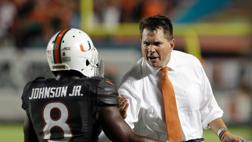 Miami Hurricanes head coach Al Golden, right, congratulates Duke Johnson (8) for scoring a touchdown against Duke in the first  half of an NCAA college football game in Miami Gardens, Fla., Saturday, Sept. 27, 2014. (AP Photo/Alan Diaz)