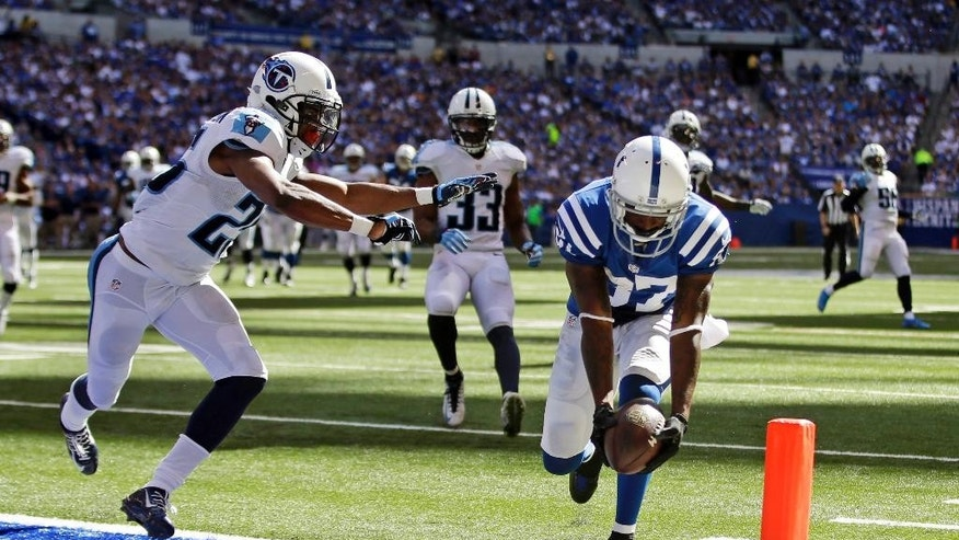 Indianapolis Colts wide receiver Reggie Wayne scores a touchdown on a 28-yard catch in front of Tennessee Titans cornerback Blidi Wreh-Wilson during the second half of an NFL football game in Indianapolis, Sunday, Sept. 28, 2014. (AP Photo/Darron Cummings)