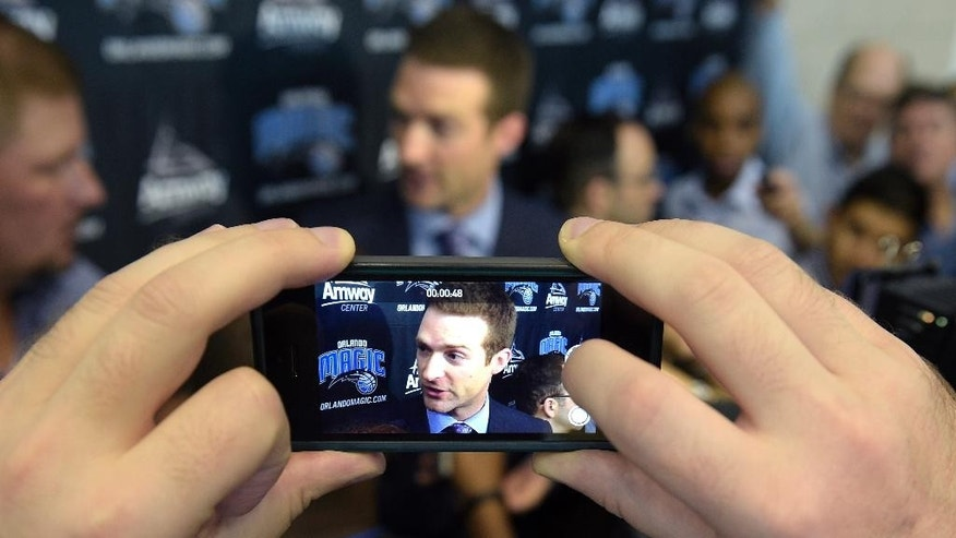 Orlando Magic general manager Rob Hennigan is seen on a reporter's phone while answering questions at the team's NBA basketball media day in Orlando, Fla., Monday, Sept. 29, 2014.(AP Photo/Phelan M. Ebenhack)