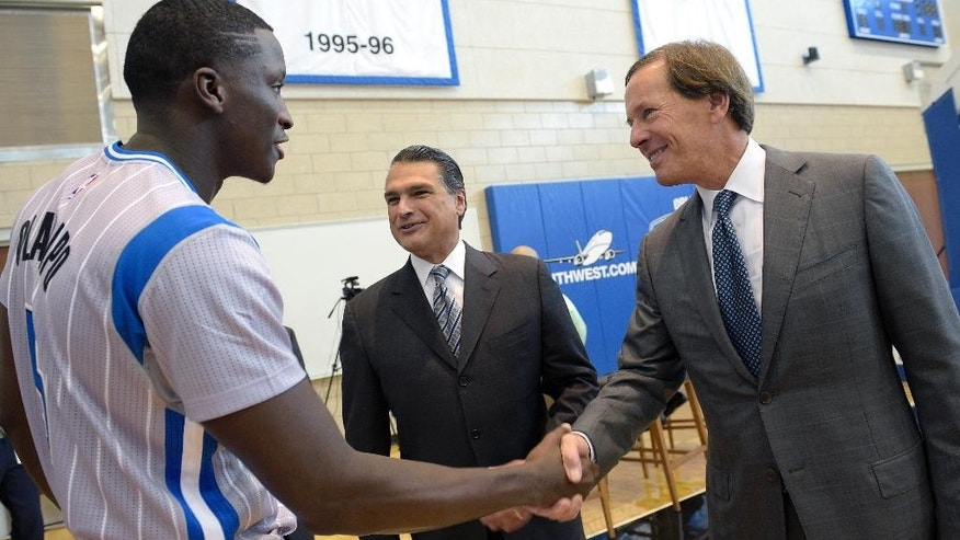 Orlando Magic guard Victor Oladipo, left, shakes hands with team chairman Dan DeVos, right, as CEO Alex Martins watches during NBA basketball media day in Orlando, Fla., Monday, Sept. 29, 2014. (AP Photo/Phelan M. Ebenhack)