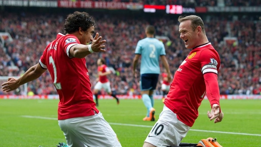Manchester United's Wayne Rooney, right, celebrates with teammate Rafael after scoring against West Ham United during their English Premier League soccer match at Old Trafford Stadium, Manchester, England, Saturday Sept. 27, 2014. (AP Photo/Jon Super)