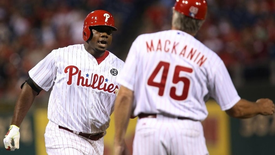 Philadelphia Phillies' Ryan Howard is congratulated by third base coach Pete Mackanin after hitting a home run in the second inning of a baseball game against the Atlanta Braves, Saturday, Sept. 27, 2014, in Philadelphia. (AP Photo/Laurence Kesterson)