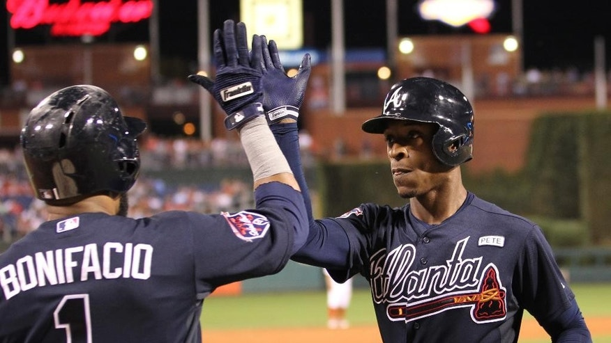 Atlanta Braves' B.J. Upton is congratulated by Emilio Bonifacio after hitting a home run in the third inning of a baseball game against the Philadelphia Phillies, Saturday, Sept. 27, 2014, in Philadelphia. (AP Photo/Laurence Kesterson)