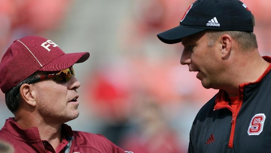 Florida State coach Jimbo Fisher, left, and North Carolina State coach Dave Doeren speak prior to an NCAA college football game in Raleigh, N.C., Saturday, Sept. 27, 2014. (AP Photo/Gerry Broome)