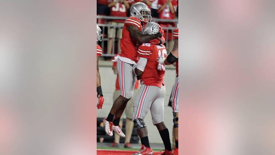 Ohio State running back Dontre Wilson, left, celebrates his touchdown catch against Cincinnati with quarterback J.T. Barrett during the third quarter of an NCAA college football game Saturday, Sept. 27, 2014, in Columbus, Ohio. Ohio State defeated Cincinnati 50-28. (AP Photo/Jay LaPrete)